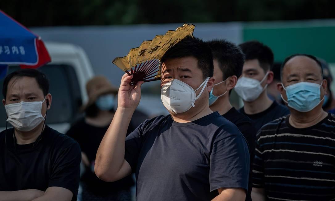 Moradores de Pequim fazem fila para serem testados para a Covid-19; a cidade reportou 25 novos casos nesta sexta Foto: NICOLAS ASFOURI / AFP