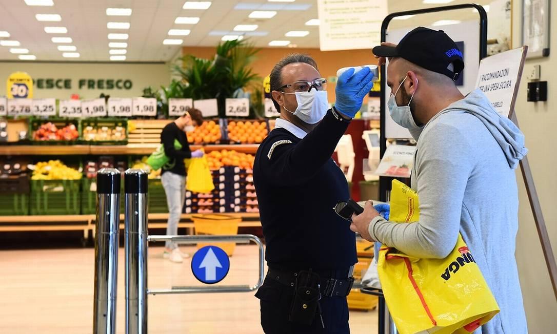 Medição de temperatura é fundamental na entrada de empresas, diz portaria (Na foto, cliente é medido ao chegar ao mercado). Foto: MASSIMO PINCA / Reuters