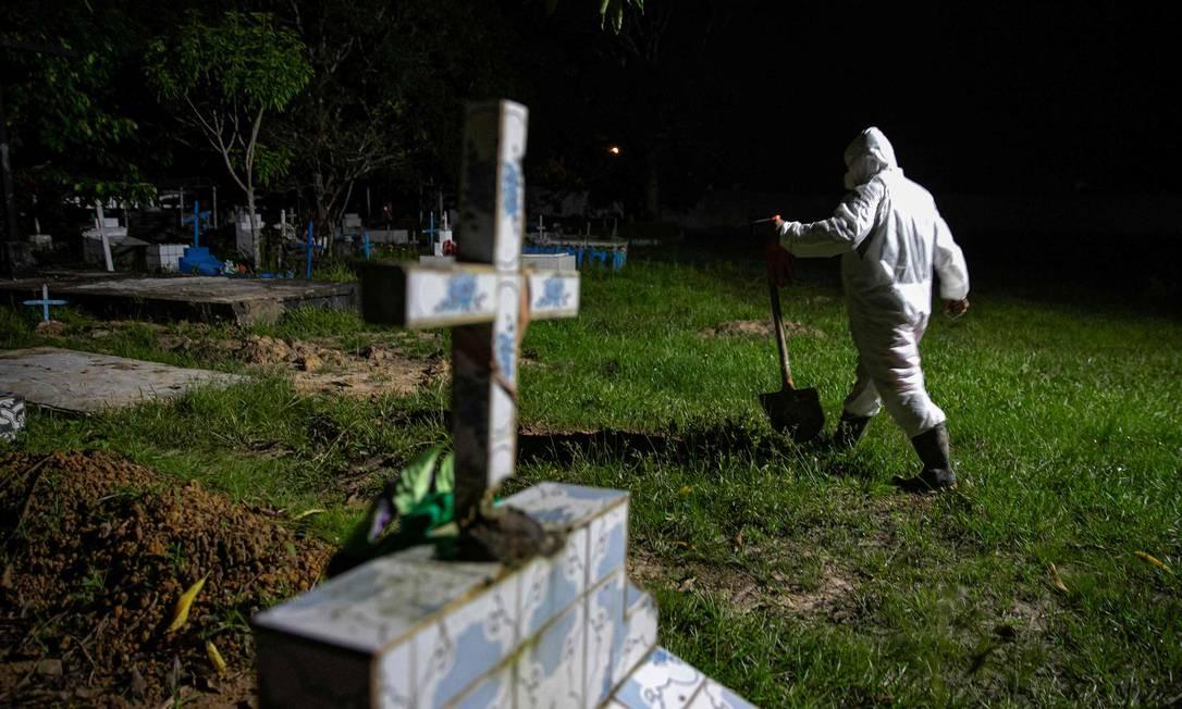 Coveiro com roupas de proteção no cemitério municipal Recanto da Paz, durante o enterro de uma vítima da COVID-19, na cidade de Breves, a sudoeste da ilha do Marajó, no Pará, em 30 de maio Foto: TARSO SARRAF / AFP