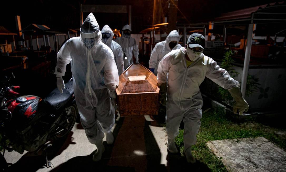 Coveiros em trajes de proteção carregam o caixão de uma vítima do novo coronavírus no cemitério Recanto da Paz, no Pará Foto: TARSO SARRAF / AFP