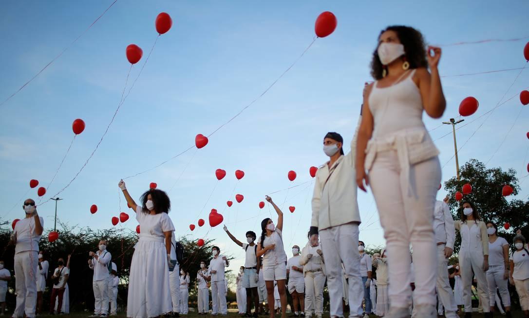 Artistas com balões vermelhos protestam em homenagem a pessoas que morreram pela COVID-19 no país, em Brasília, em 1º de junho Foto: ADRIANO MACHADO / REUTERS