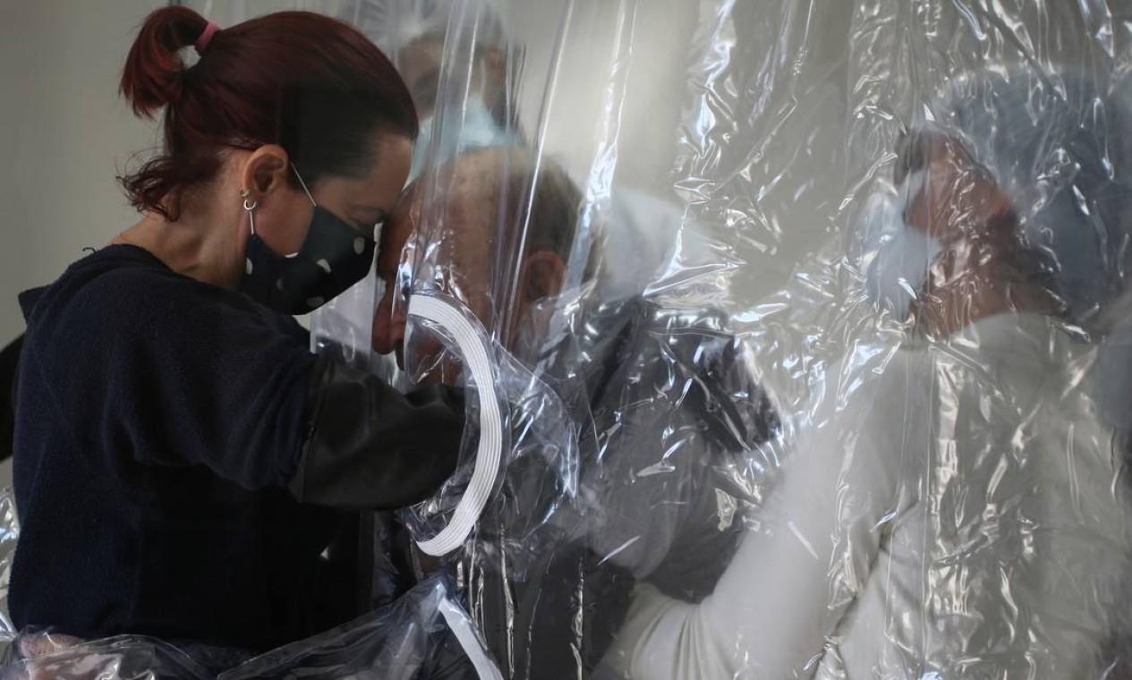 Suzana Lisboa abraça seu pai, Raul Lisboa, 89 anos, através de uma cortina de plástico instalada em abrigo para idosos em São Paulo Foto: RAHEL PATRASSO / REUTERS
