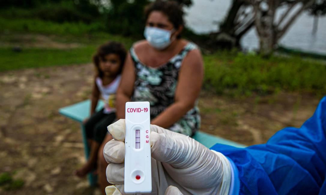 Um agente de saúde mostra um teste Covid-19 na comunidade ribeirinha de Roli Madeira Foto: TARSO SARRAF / AFP
