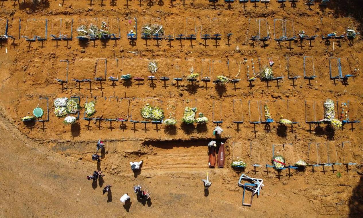Imagem de coveiros enterrando uma pessoa no cemitério de Nossa Senhora Aparecida, no bairro de Tarumã, em Manaus, durante pandemia de coronavírus Foto: MICHAEL DANTAS / AFP