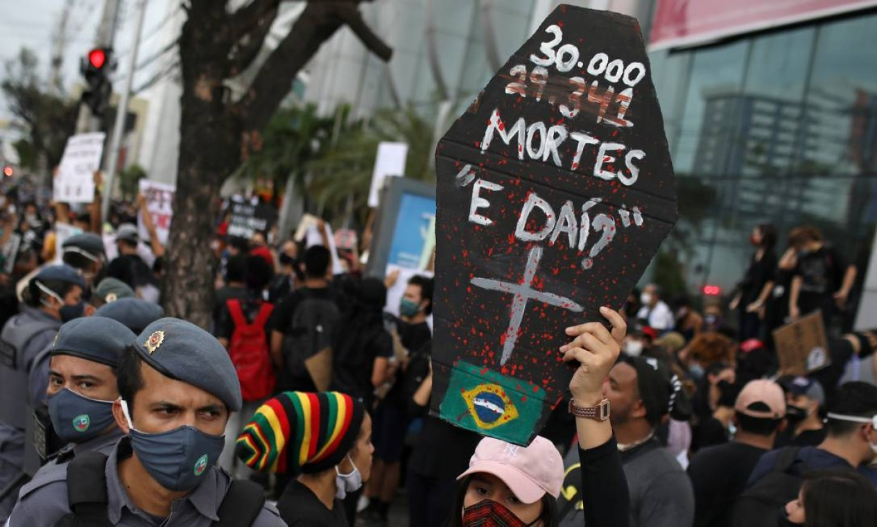"""Manifestante contrário ao governo brasileiro segura um cartaz representando o caixão de uma vítima da Covid-19 com a mensagem """"30.000 mortes, e daí?"""", durante um protesto chamado """"Amazonas pela Democracia"""", em referência à fala do presidente Bolsonaro Foto: BRUNO KELLY / REUTERS"""