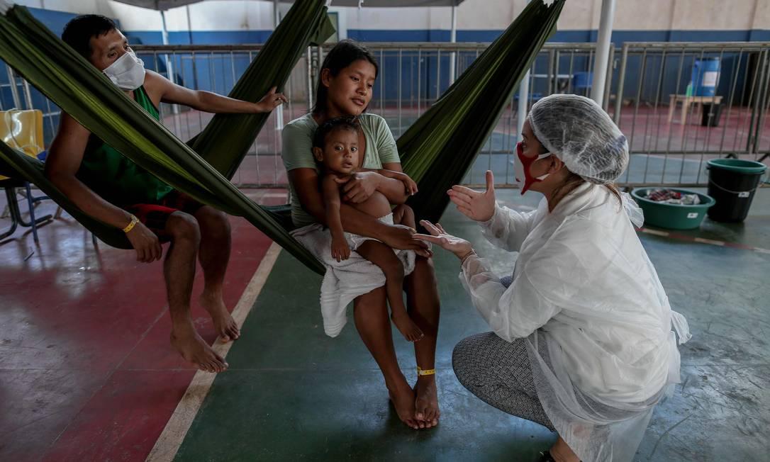 Membro do Médicos Sem Fronteiras olha para um garoto da tribo Warao, o segundo maior grupo indígena da Venezuela, que sofre de sintomas do novo coronavírus, em Manaus, no Amazonas, em 3 de junho Foto: MICHAEL DANTAS / AFP