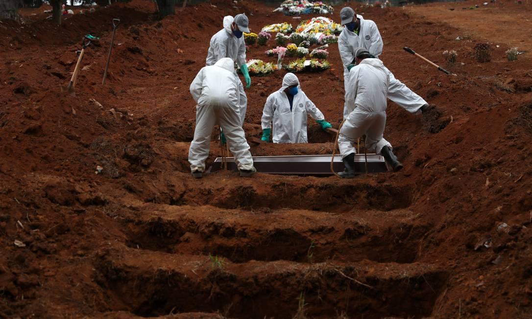 Coveiros vestindo roupas de proteção enterram o caixão de uma vítima da COVID-19, no cemitério São Luiz, em São Paulo. Até o mês de abril, o Brasil registrou mais mortes por Covid-19 do que todo o ano de 2020, quando começou a pandemia, e também ultrapassou a triste marca dos 400 mil mortos Foto: AMANDA PEROBELLI / Reuters - 04/07/2020
