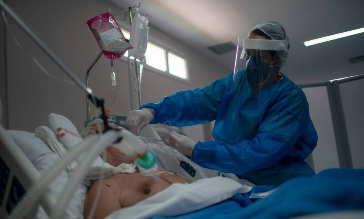 Profissional de saúde cuida de um paciente na enfermaria da Unidade de Terapia Intensiva (UTI), onde pacientes infectados com o novo coronavírus estão sendo tratados no Hospital Público Doutor Ernesto Che Guevara, na cidade de Maricá, no Rio de Janeiro Foto: MAURO PIMENTEL / AFP