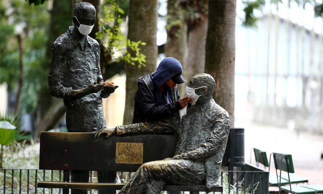 Uma mulher toca as estátuas dos escritores brasileiros Mário Quintana e Carlos Drummond de Andrade com máscaras, em Porto Alegre, em 7 de junho Foto: DIEGO VARA / REUTERS
