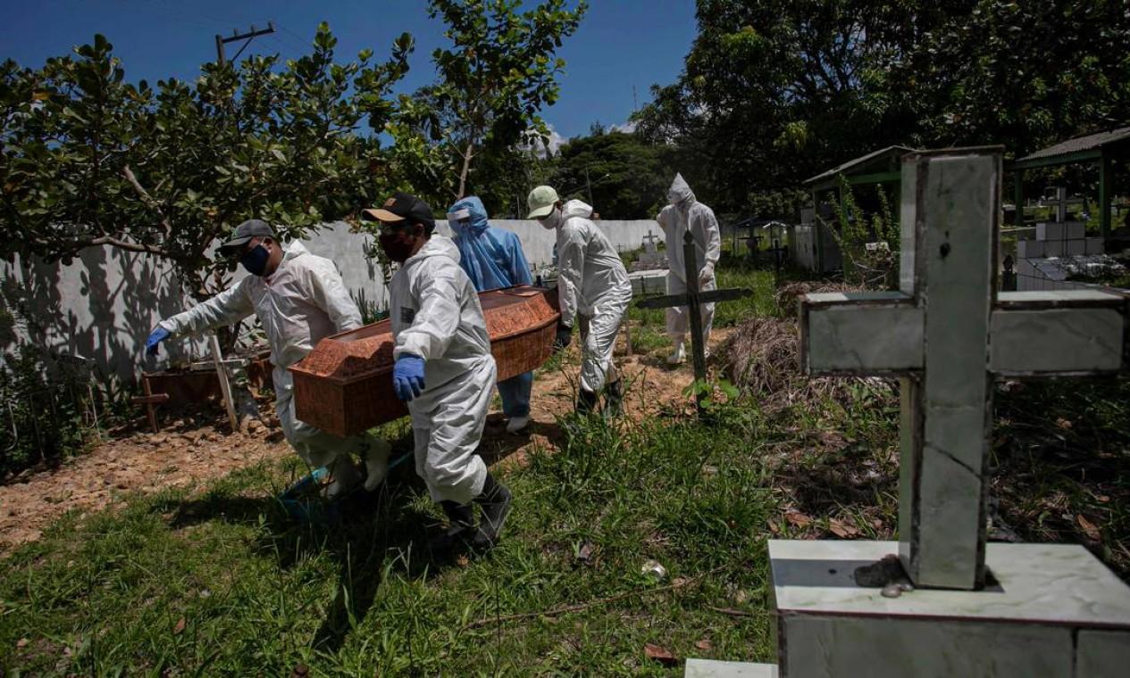 Sepultadores carregam um caixão de vpitima da Covid-19 no cemitério municipal Recanto da Paz, em Breves, no Pará, em 7 de junho Foto: TARSO SARRAF / AFP