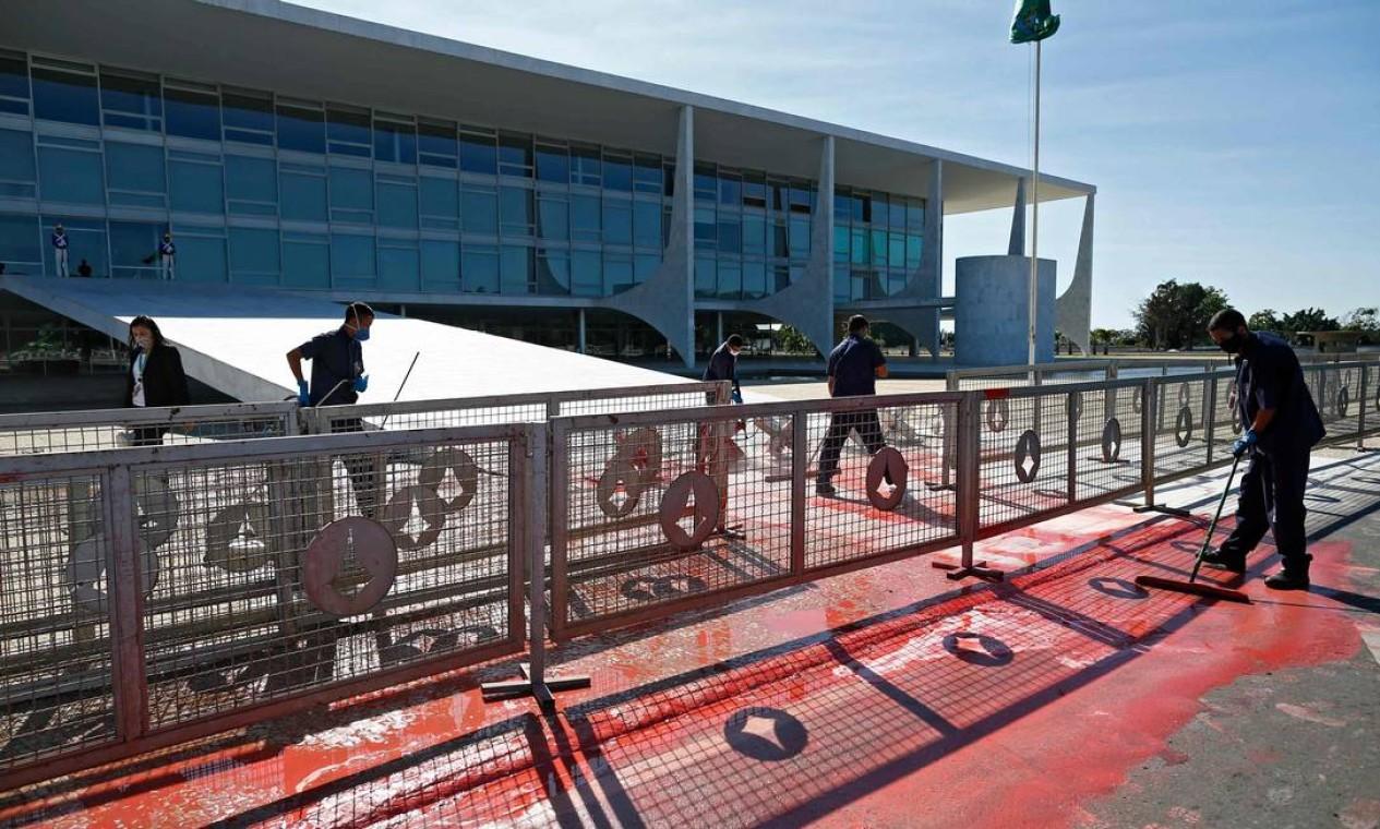 Funcionários limpam tinta vermelha derramada por um manifestante na rampa de acesso do Palácio do Planalto, em Brasília, em 8 de junho Foto: SERGIO LIMA / AFP