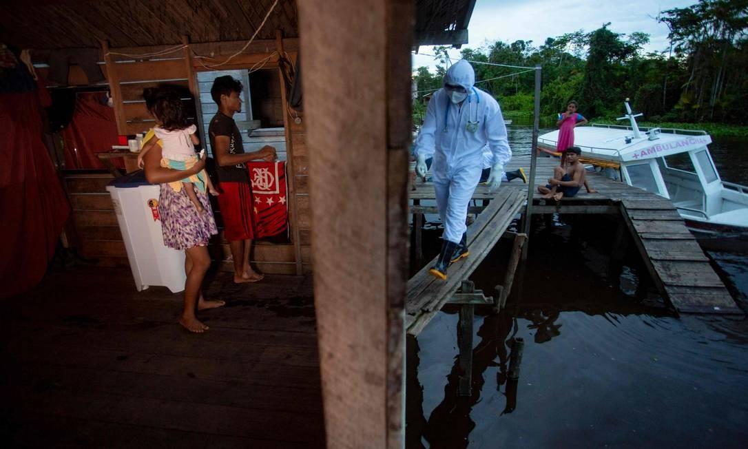 Um profissional de saúde da cidade de Melgaço chega a uma pequena comunidade ribeirinha no rio Quará, onde oito famílias vivem sem eletricidade, para prestar assistência médica a seus moradores em meio à disseminação do coronavírus, no sudoeste de Marajó Ilha, no Pará, Brasil, em 9 de junho Foto: TARSO SARRAF / AFP