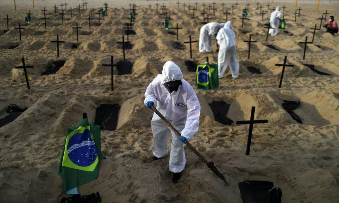 Ativistas da ONG Rio de Paz em trajes de proteção cavam sepulturas na praia de Copacabana para simbolizar os mortos pela COVID-19, durante uma manifestação no Rio de Janeiro, em 11 de junho Foto: PILAR OLIVARES / REUTERS