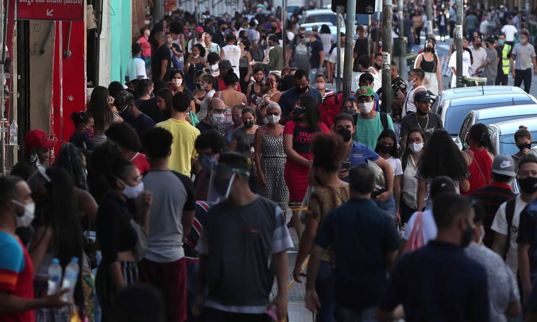 As pessoas caminham por uma rua comercial em São Paulo, enquanto a cidade relaxa as restrições e permite a abertura do comércio, em 11 de junho Foto: AMANDA PEROBELLI / REUTERS
