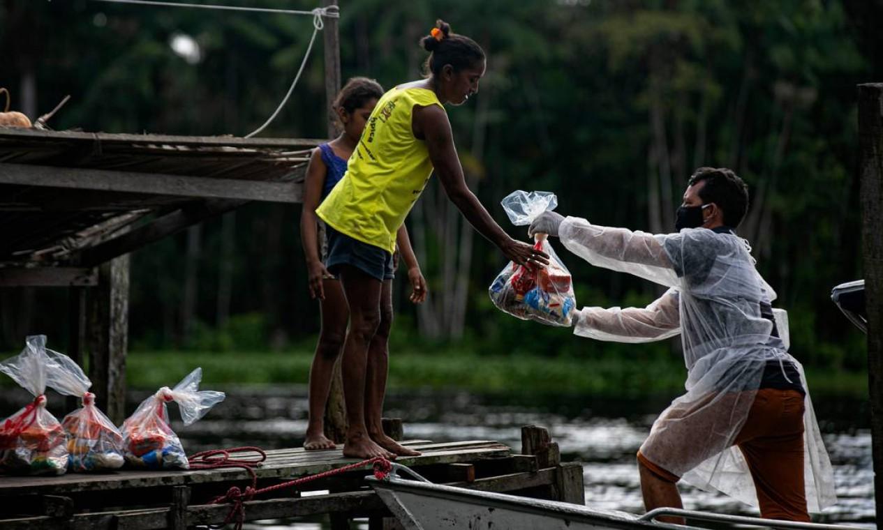 Funcionário do Ministério da Educação entrega kits de merenda escolar para locais carentes em Megalço, no Pará, Brasil Foto: TARSO SARRAF / AFP