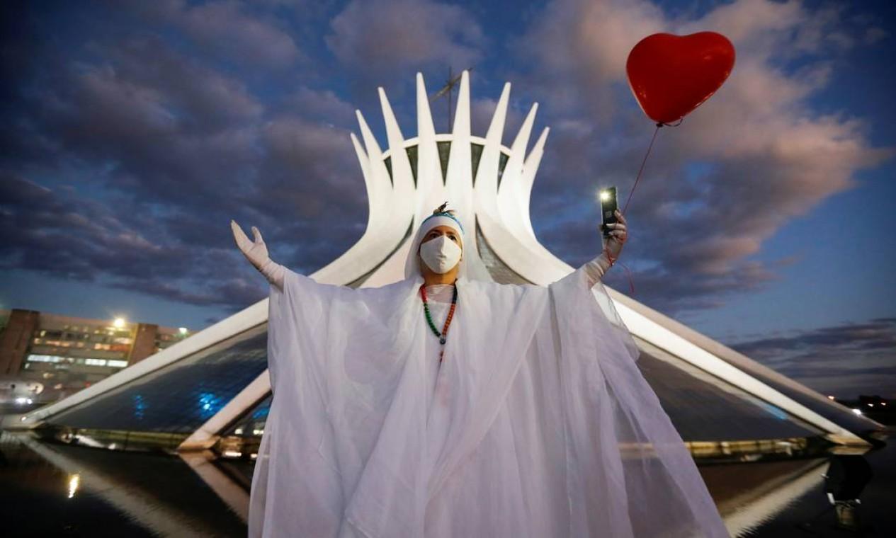 Artista se apresenta com um balão vermelho em forma de coração durante um protesto em homenagem a pessoas que morreram pela Covid-19 no Brasil, em Brasília, em 15 de junho Foto: ADRIANO MACHADO / REUTERS