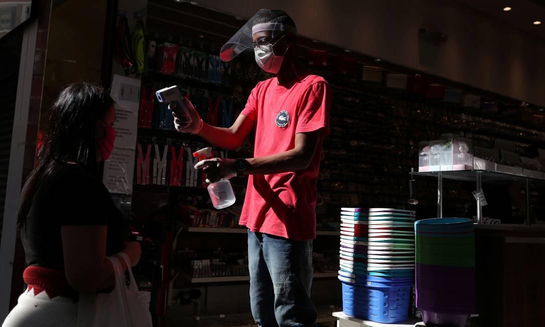 Um funcionário mede a temperatura de um cliente na entrada de uma loja, em São Paulo, em 19 de junho Foto: AMANDA PEROBELLI / REUTERS