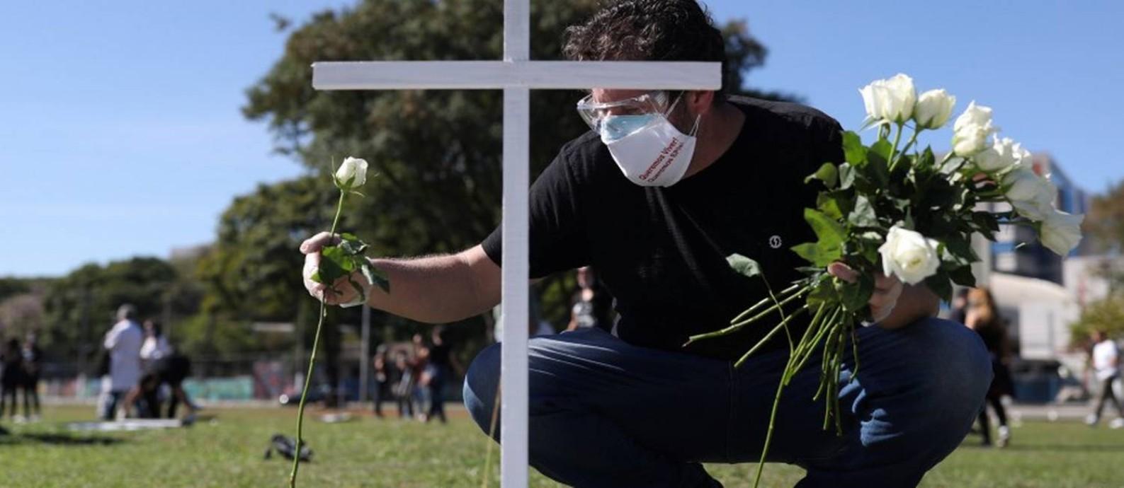 Homem coloca uma flor diante de uma cruz simbólica num protesto e homenagem a profissionais da saúde mortos pela Covid-19 em São Paulo Foto: AMANDA PEROBELLI / REUTERS