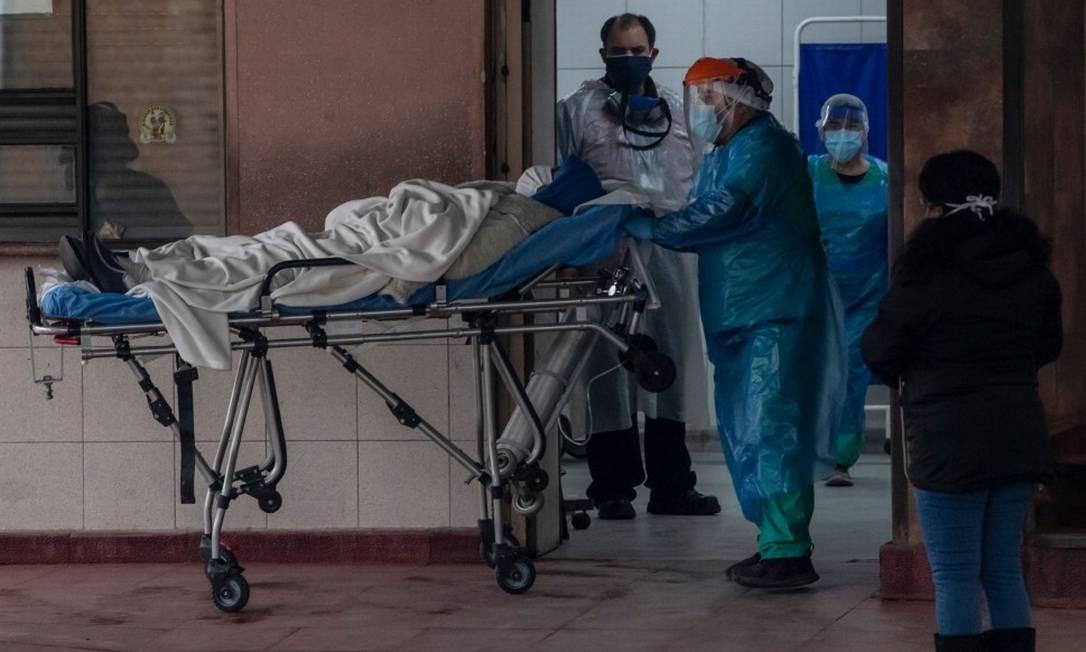 No Hospital San Jose, em Santiago, profissionais da Saúde transferem um paciente com Covid-19 Foto: MARTIN BERNETTI / AFP