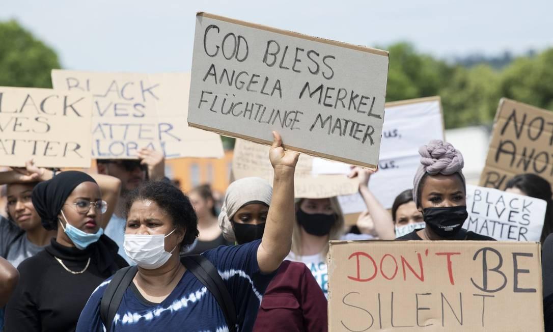 """Mulher segura cartaz que diz: """"Deus abençoe Merkel, refugiados importam"""", durante manifestação contra o racismo em Stuttgart Foto: THOMAS KIENZLE / AFP"""