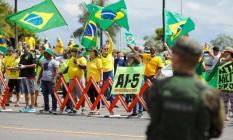 Apoiadores do presidente Jair Bolsonaro exibem cartaz com alusão ao AI-5 no Dia do Exército, em Brasília Foto: SERGIO LIMA / AFP