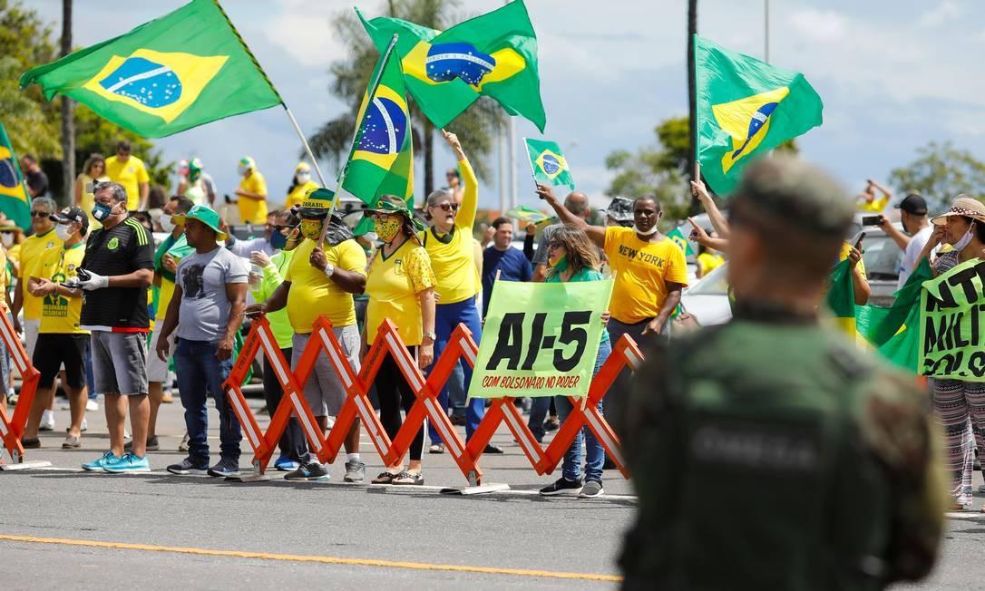 Apoiadores do presidente Jair Bolsonaro exibem cartaz com alusão ao AI-5 no Dia do Exército, em Brasília Foto: Sergio Lima / AFP/19-04-2020