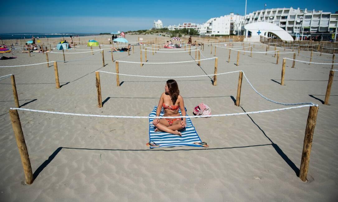 Uma mulher toma sol em Sunset beach, em uma área isolada de distanciamento marcada pelo município ao longo das praias de La Grande Motte, sul da França, enquanto o país facilita as medidas de bloqueio tomadas para conter a propagação da pandemia de COVID-19 Foto: CLEMENT MAHOUDEAU / AFP