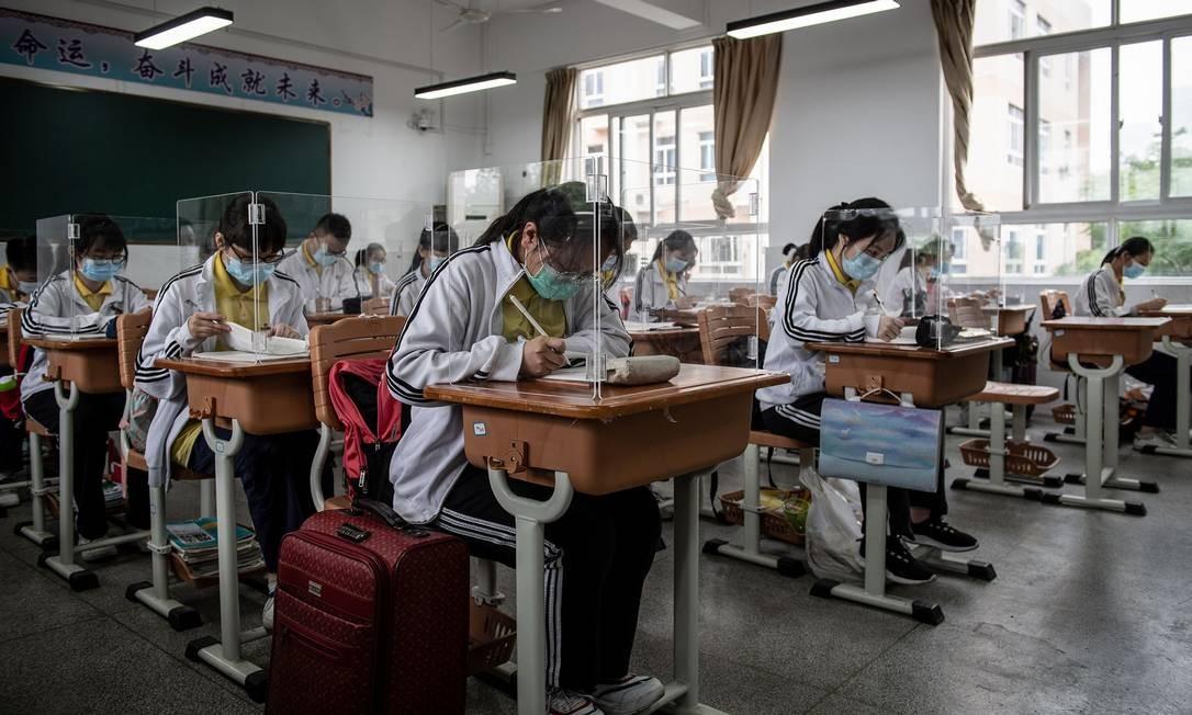Alunos do ensino médio estudam com divisórias de plástico em uma sala de aula em Wuhan, na província central de Hubei, na China Foto: STR / AFP