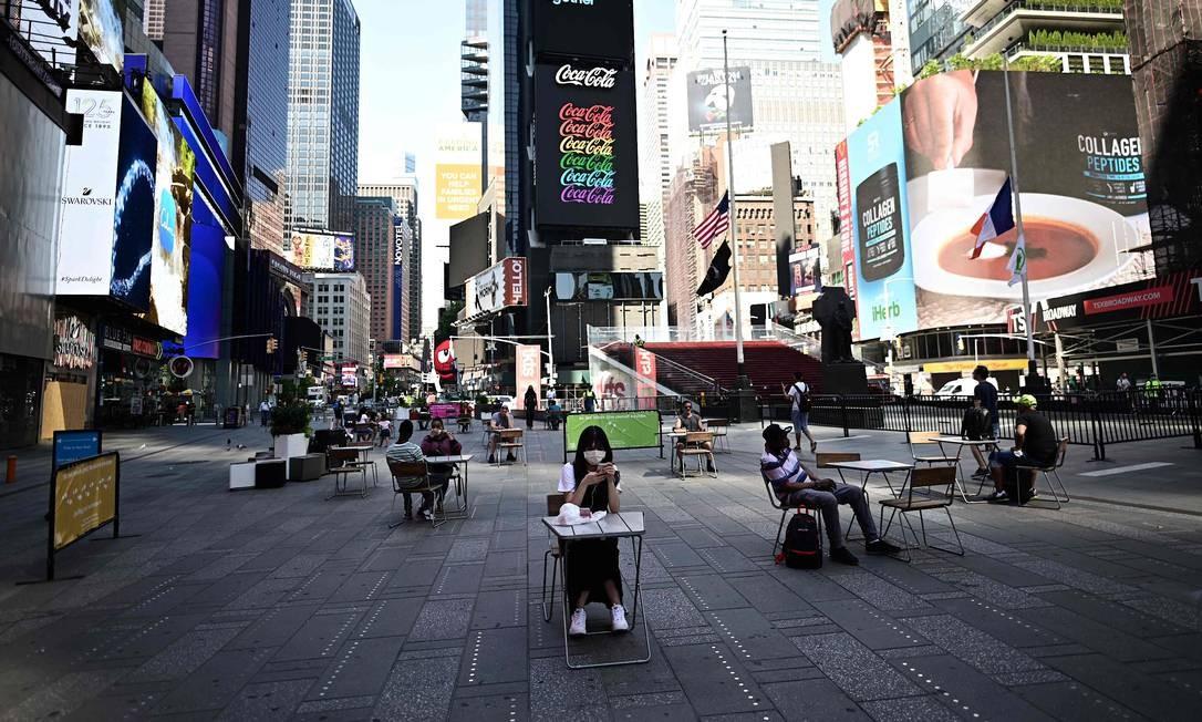 Pessoas se sentam nas mesas, respeitando o distanciamento social, na Times Square. A cidade de Nova York entra na segunda fase da reabertura em 22 de junho. As pessoas voltam a poder comer ao ar livre em restaurantes, e barbearias e salões de beleza também podem abrir com 50% da capacidade Foto: JOHANNES EISELE / AFP