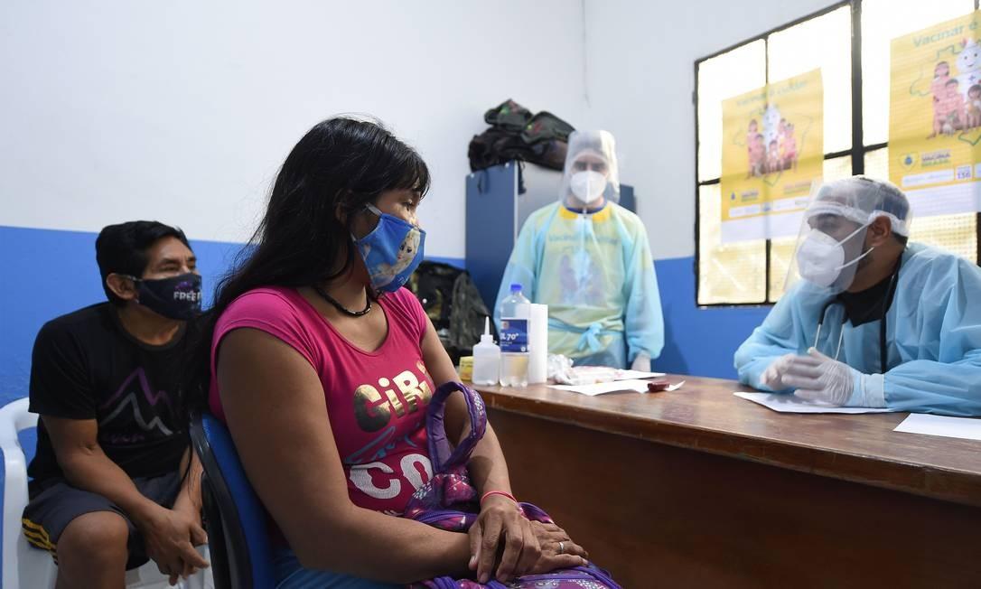 Os indígenas brasileiros Anita e Nilton, do grupo étnico Marubo, são notificados de que contraíram o novo coronavírus. Quem deu o diagnóstico foi um membro da equipe médica das Forças Armadas do Brasil no posto de saúde de Atalaia do Norte, estado do Amazonas. Foto: EVARISTO SA / AFP
