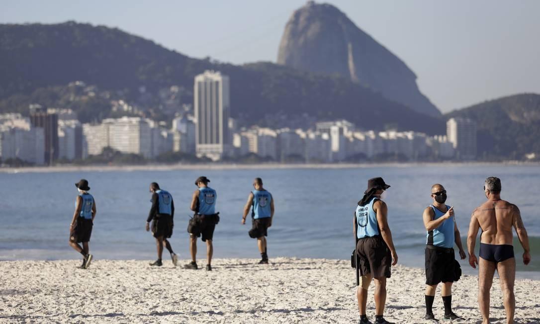 Agentes da Guarda Municipal do Rio retiram banhistas das areias da Praia de Copacabana, na Zona Sul da cidade Foto: Luiza Moraes / Agência O Globo