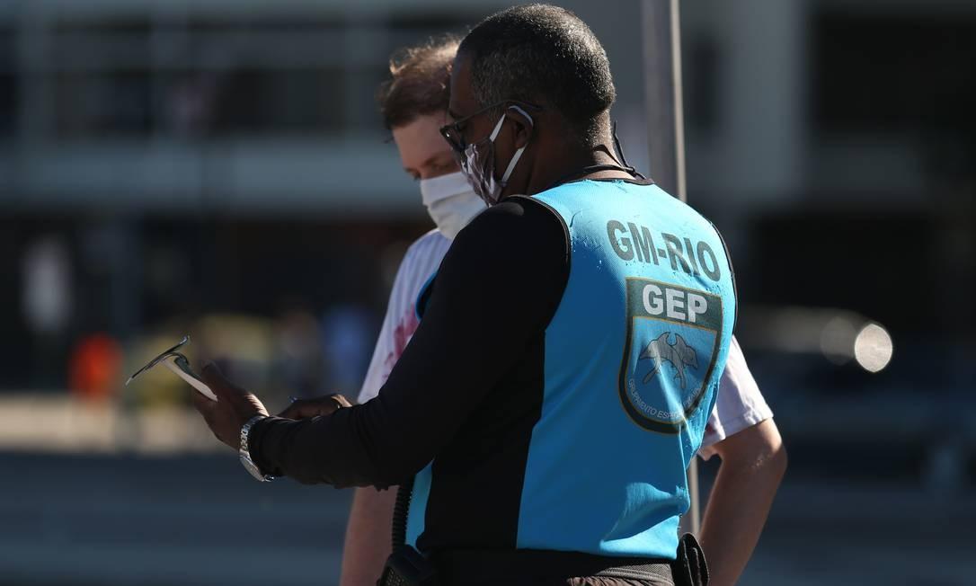 Guarda aplica multa a pedestres que não estão usando máscaras no calçadão de Copacabana Foto: Luiza Moraes / Agência O Globo
