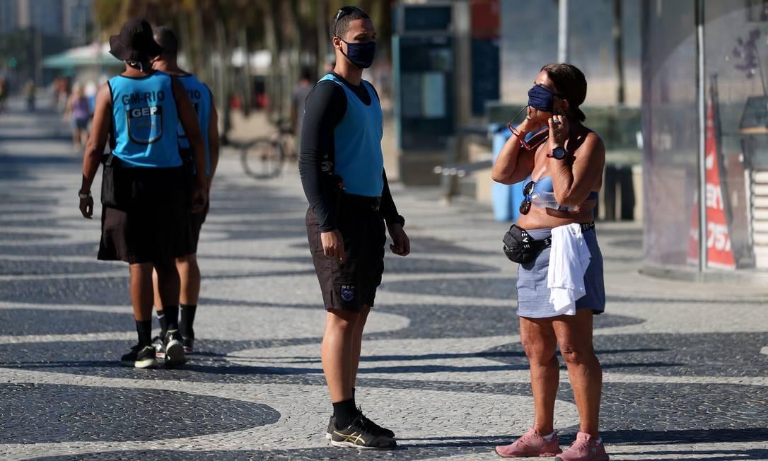 Guarda orienta pedestre a utilizar máscara, no calçadão de Copacabana. Agentes aplicaram multas a quem desrespeitava a regra nesta segunda-feira (22) Foto: Luiza Moraes / Agência O Globo