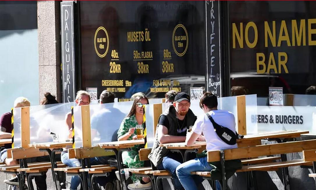Telas entre as mesas protegem clientes sentados ao ar livre em um restaurante no centro de Estocolmo Foto: AFP