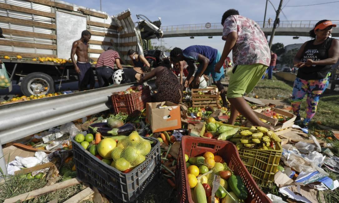 Carga de frutas, legumes e verdura atraiu moradores do entorno da rodovia Foto: Gabriel de Paiva / Agência O Globo