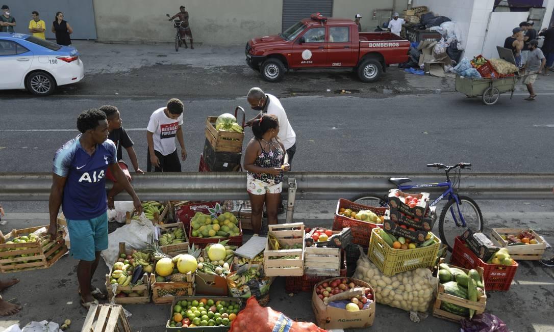 Moradores de áreas vizinhas ao acidente recolhem alimentos do caminhão que tombou Foto: Gabriel de Paiva / Agência O Globo