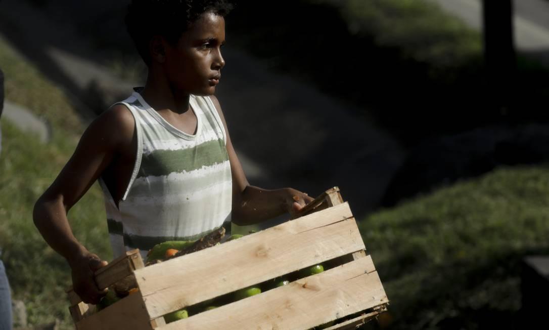 Criança carrega caixote com frutas Foto: Gabriel de Paiva / Agência O Globo