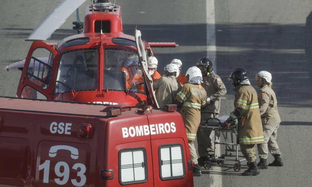 Bombeiros levam vítima de acidente ao helicóptero Foto: Gabriel de Paiva / Agência O Globo