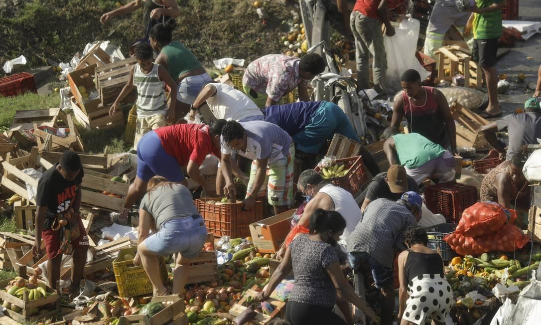 Dezenas de pessoas recolhem alimentos que estavam espalhados pela pista Foto: Gabriel de Paiva / Agência O Globo
