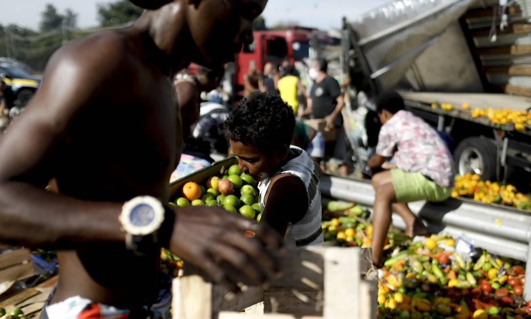 Pessoas recolhem os alimentos que eram transportados pelo caminhão que virou Foto: Gabriel de Paiva / Agência O Globo
