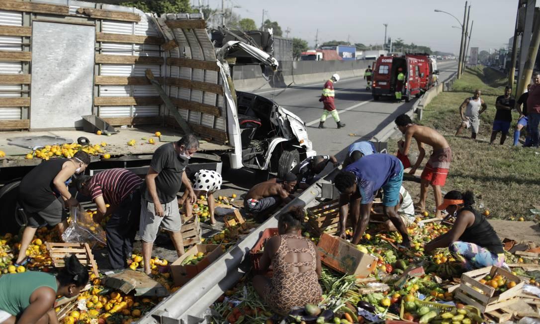 Pessoas catam comida enquanto socorristas trabalham no atendimento às vítimas do acidente que aconteceu por volta das 8h, nesta terça-feira Foto: Gabriel de Paiva / Agência O Globo