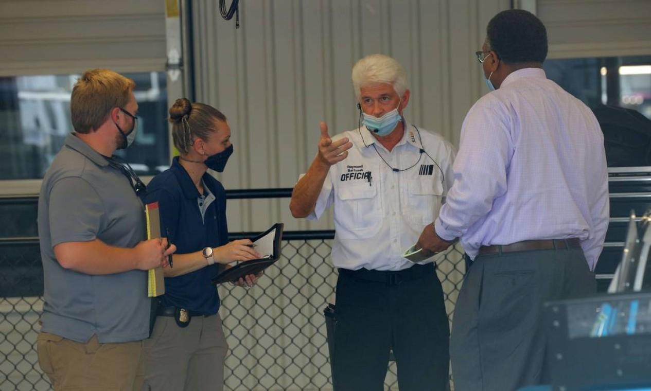 Investigadores falam com o funcionários na área da garagem antes da prova prova GEICO 500, em 22 de junho, em Talladega. Ameaça racista contra o piloto Bubba Wallace fez a Nascar abrir uma investigação Foto: Chris Graythen / AFP