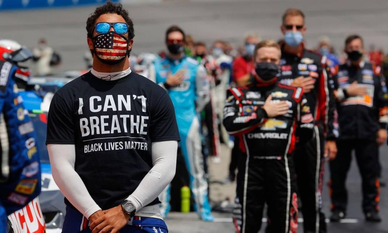 """Bubba Wallace, em em foto tirada em 6 de junho, canta o hino nacional vestido com uma camiseta com a frase """"Não consigo respirar - vidas negras importam"""" sob seu traje de corrida. Protesto solitário em solidariedade aos manifestantes de todo o mundo que tomavam as ruas após a morte de George Floyd, em 25 de maio Foto: CHRIS GRAYTHEN / AFP"""
