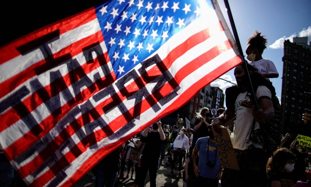 """Crianaça negra sobre os ombros do pai segura bandeira dos Estados Unidos com a a frase """"eu não consigo respirar"""", dita por George Floyd enquanto era asfixiado até a morte pelo policial Derek Chauvin Foto: EDUARDO MUNOZ / REUTERS"""
