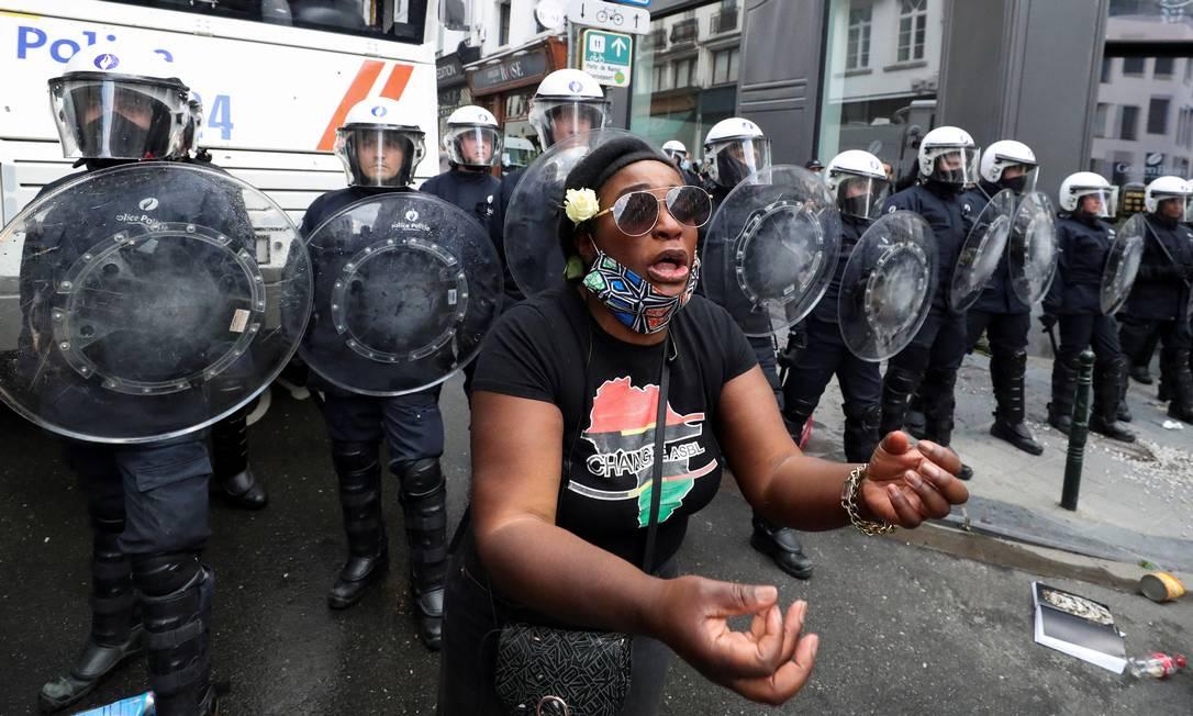 Manifestante gesticula diante de policiais de choque, em protesto do movimento Black Lives Matter (Vidas Negras Importam), no centro de Bruxelas, Bélgica Foto: YVES HERMAN / REUTERS