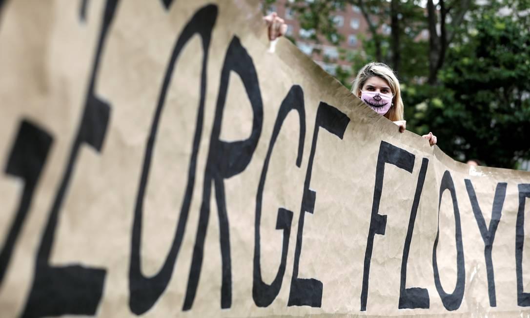 Pessoas seguram uma faixa com o nome de George Floyd, no bairro de Brooklyn, em Nova York Foto: ANDREW KELLY / REUTERS