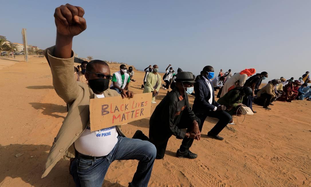 Senegaleses se ajoelham e erguem o punho cerrado, gesto eternizado pelo movimento Panteras Negras, durante a luta por direitos civis nos EUA, em protesto em Dakar Foto: ZOHRA BENSEMRA / REUTERS