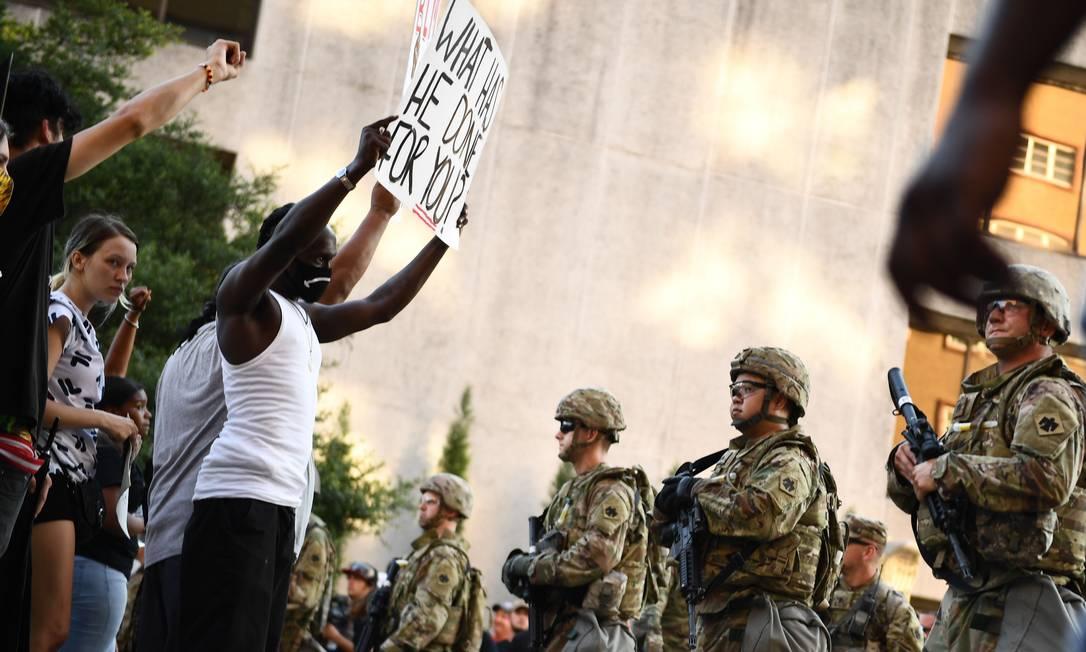 """Manifestantes confrontam a polícia em Tulsa, Oklahoma. Para conter a revolta do povo, Trump deu carta branca para governadores solicitarem apoio da Guarda Nacional. Em um publicação no Twitter, que chegou a ser advertido pela própria rede social devido ao caráter ameaçador e violento, o presidente dos EUA, Donald Trump, se manifestou sobre os protestos: """"quando o saque começar, começam os tiros"""" Foto: BRENDAN SMIALOWSKI / AFP"""