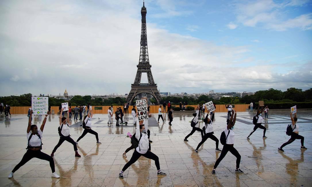 Membros do grupo de ioga de Hermine Prunier exibem cartazes enquanto executam uma coreografia de uma música indiana pela paz mundial e protestam para mostrar seu apoio ao movimento Black Lives Matter, em Paris, durante o Festival de Música da França Foto: ABDULMONAM EASSA / AFP