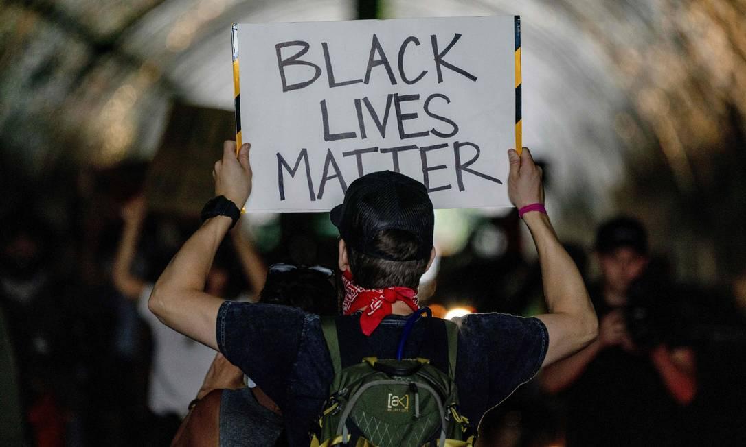 Manifestante, em Los Angeles, California, segura cartaz com o lema que dá nome ao movimento antirracista que se espalhou pelo mundo: vidas negras importam Foto: KYLE GRILLOT / AFP